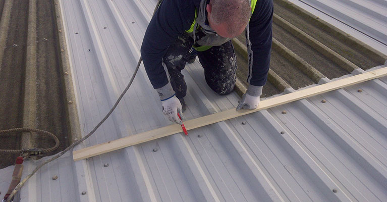 IRM roofing expert wearing a safety harness