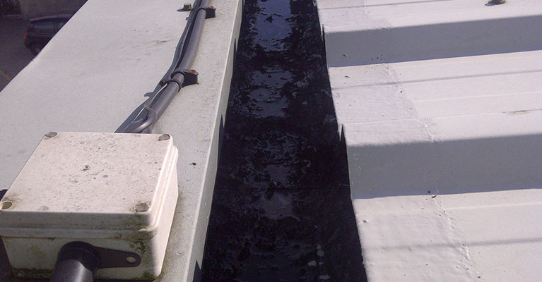 Industrial roof gutter before being cleaned
