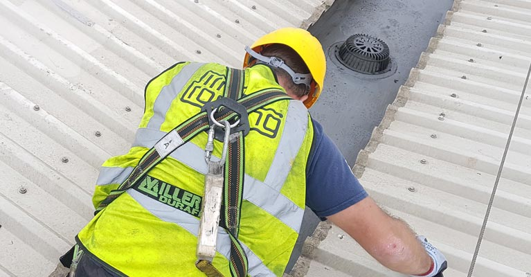 IRM Roofing operative clipped onto existing safety line whilst working on the roof.