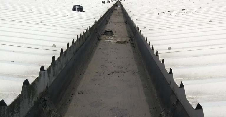 Completed view of industrial gutter cleanout with just leaf guards to be re-positioned.