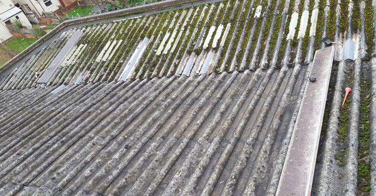 A half finished view of the moss being removed from the industrial roof.