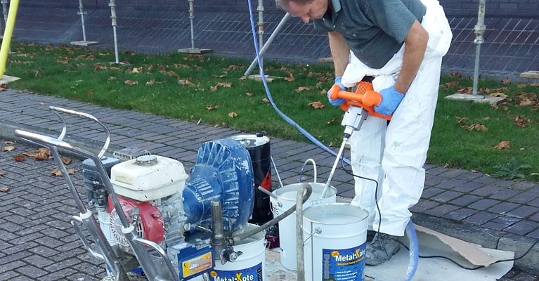 Mixing Acrypol Metalkote next to the Graco paint spraying machine.
