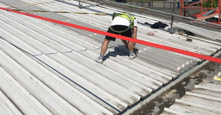 IRM roofer fixing down roof lights whilst harnessed and attached to a torque tensioned safety line.
